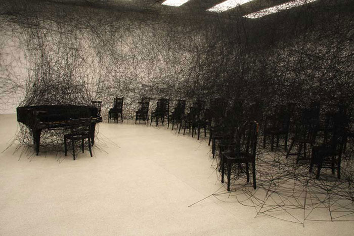Room-sized art installations of ominous black webs