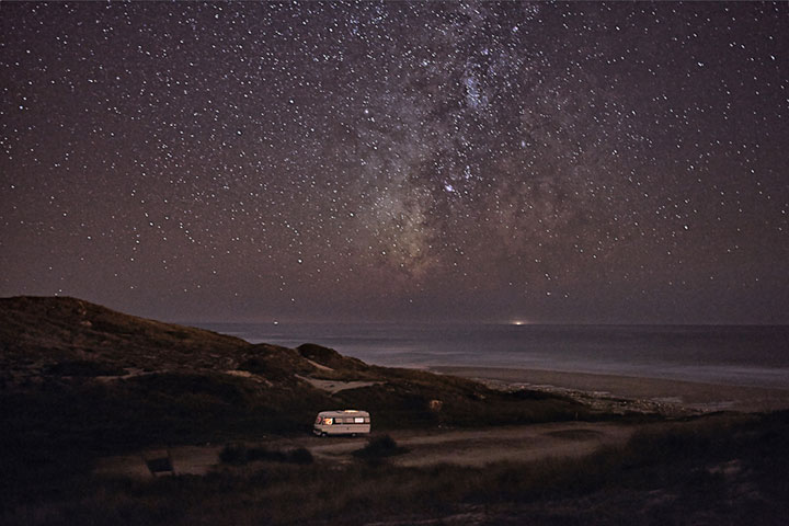 Epic photographs of a traveling van dwarfed by starry skies